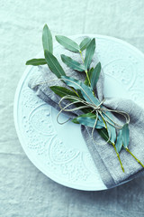 Place setting with linen napkin and green twig on linen table cloth. Flat lay. Copy space. Natural home design