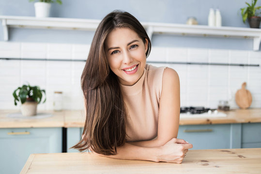 Beautiful young woman relaxing at the kitchen. Happy smiling girl home portrait. Resting, relaxation and leisure concept