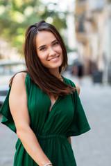 Fototapeta Fashion model wearing green overall posing outdoor. Young beautiful brunette caucasian woman walking summer streets. Beautiful girl, urban portrait.
