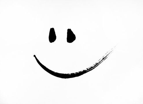 Simple smiley smiley face in black painted on a piece of paper.