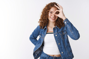 Positive lucky cute caucasian redhead curly-haired girl freckles pimples smiling broadly show okay nice gesture look through circle amused carefree, having fun satisfied everything, white background