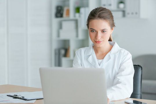 Female doctor working on laptop in clinic