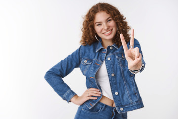 Blurred ginger girl standing behind extend arm forward show camera victory peace gesture smiling broadly hold hand waist confident self-assured pose, standing happily white background feel lucky
