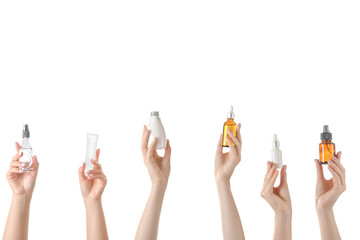 Female hands with different cosmetic products in bottles on white background