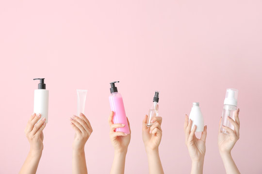 Female hands with different cosmetic products in bottles on color background