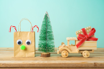 Christmas holiday background with paper bag, gift box in toy truck and pine tree on wooden table.