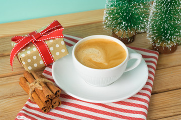 Christmas holiday background with coffee cup, gift box and pine tree on wooden table.