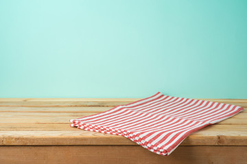 Empty wooden table with tablecloth over blue background