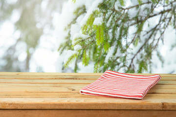 Empty wooden table with tablecloth over snow pine tree branches background
