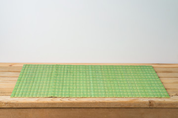 Empty wooden table with green bamboo placemat. Chinese kitchen or restautant concept background