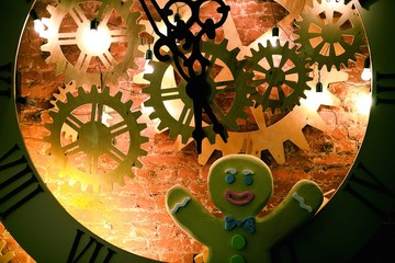 Gingerbread man standing next to gignt clock