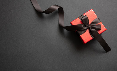 Wall Mural - Gift box with black ribbon against black background, Black Friday concept.