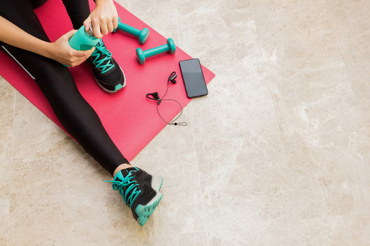 Stock photo of a young woman resting after exercising at home in the living room with a bottle