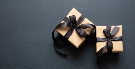 Wall Mural - Gifts with black ribbon against black background, Black Friday concept.