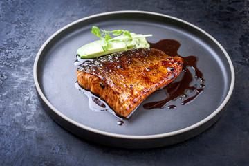 Minimalistic design Japanese salmon fish filet with avocado and wasabi creme glazed in teriyaki sauce as closeup on a modern design plate