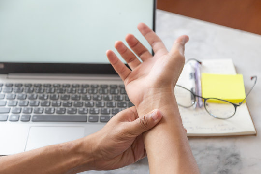 Asian freelance man is feeling pain in his wrist after using laptop in long time , office syndrome concept