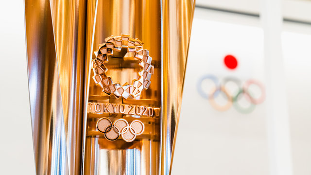 Tokyo, Japan - Nov 1, 2019: Gold trophy cup of Tokyo Summer Olympic 2020 show in Japan Olympic Museum, Olympic games logo in background. International sport event, or tournament host country concept