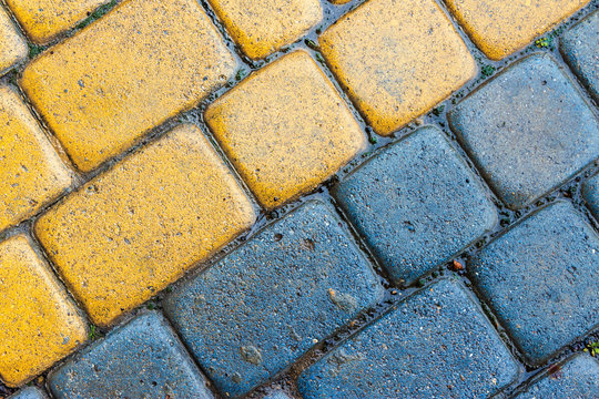 yellow and blue cobbles of pavement texture. stone masonry floor covering close up. top view of wet diagonal grungy background
