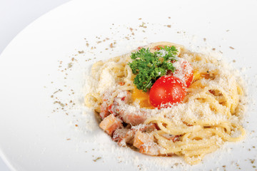 typical spaghetti alla carbonara  with raw egg and bacon. served on a white plate with grated Pecorino cheese. decorated with cherry tomato and parsley. side view