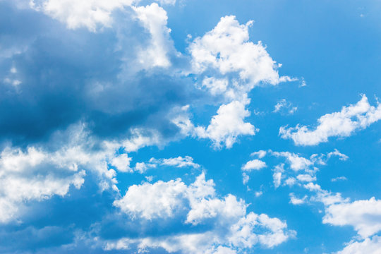 azure sky with fluffy clouds. beautiful springtime nature background. dynamic side lit cloudscape