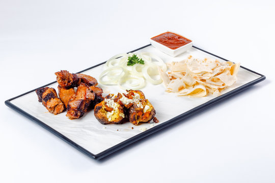 grilled pork and baked potato with cheese. onion circles and pita bread, red sauce on a white board. great snack dish for beer