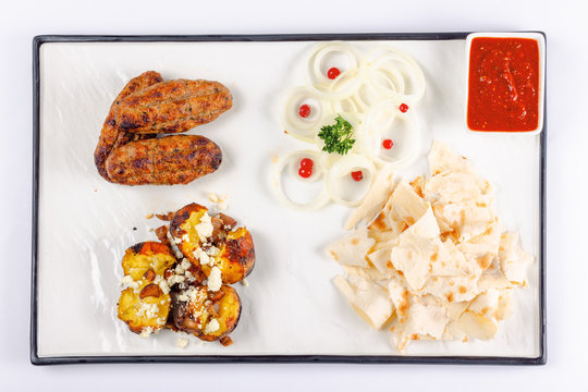 kebab and baked potato with cheese. onion circles and pita bread, red sauce on a white board. great snack dish for beer. top view flat layout
