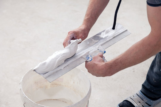 Puttyer holding spatula with putty solution. Indoors construction works concept. Builder puts decorative cement plaster to trowel in construction bucket ready for plastering