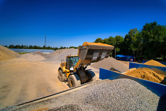Sand quarry, excavating equipment, bulldozer with heap of sand and gravel in background. Selective focus.