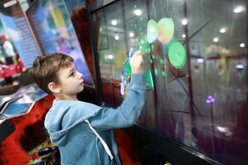 Kid playing game on touchscreen