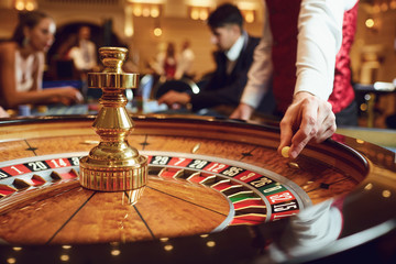 Hand of a croupier with a ball on a roulette wheel during a game in a casino.