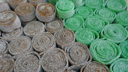 Licorice rolls, sugared, beige, black, green, background, texture, close up,