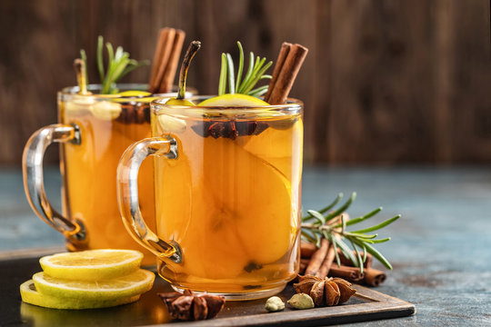 Hot drink cocktail for New Year, Christmas, winter or autumn holidays..Toddy. Mulled pear cider or spiced tea or grog with lemon, pear, cinnamon, anise, cardamom, rosemary.