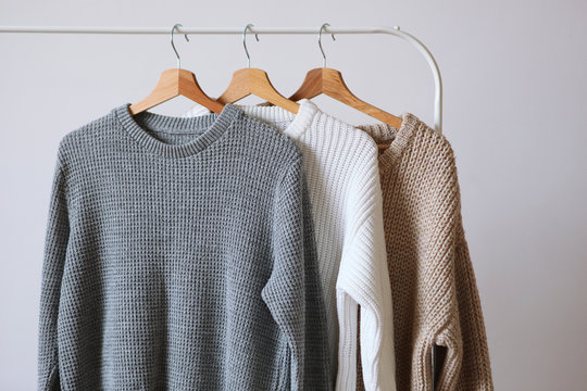 Warm sweaters on a wardrobe hanger on a light background. Autumn, winter clothes.