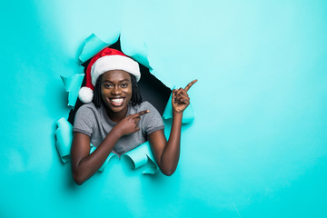 Young african woman wear in santa hat pointed with hand on copy space standing in green torn paper...