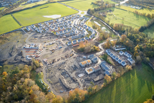 Large housing development aerial view in construction on rural countryside site Scotland UK