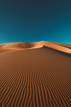 Vertical shot of a peaceful desert under the clear blue sky captured in Morocco