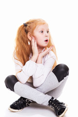 Wall Murals kids room Surprised girl sitting on a white background