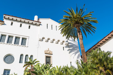 A palm tree and a white Spanish architecture style building with ornate windows and trim under a beautiful blue sky