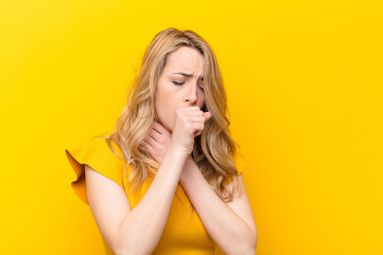 young pretty blonde woman feeling ill with a sore throat and flu symptoms, coughing with mouth covered against flat color wall
