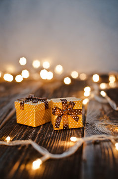 Christmas gift box lay on a wooden table on a background bokeh of festive lights.