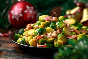 Christmas Brussel Sprouts and Bacon with decoration, gifts, green tree branch on wooden rustic table