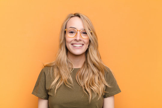 young pretty blonde woman looking happy and pleasantly surprised, excited with a fascinated and shocked expression against flat color wall