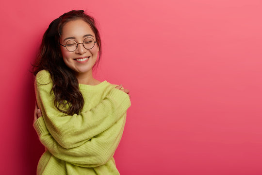 Photo of charming woman expresses self love and care, enjoys wearing new soft green sweater, embraces own body, recalls romantic moment with boyfriend, smiles pleasantly, stands over rosy wall