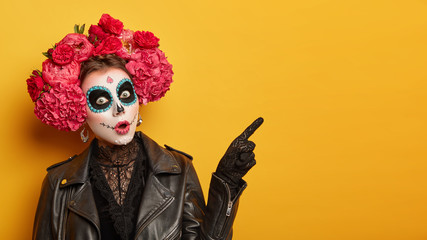 Deurstickers Carnaval Shocked female wears creative sugar skull makeup, wreath made of red peonies, celebrates All Souls day, holiday in Mexico points away with index finger isolated over yellow background shows copy space