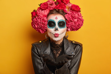 Photo of lovely woman blows mwah, keeps lips folded, wears creative makeup, prepares for carnival, prepares for Day of Dead, expresses love, poses against yellow background. Mexican female sends kiss