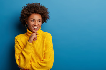 Positive curly young woman dressed in yellow comfortable sweater, holds chin, looks aside with dreamy expression, has interesting idea in mind, isolated over blue background. Ethnicity concept