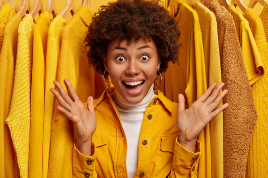 Wow, look how much clothes I have. Joyous emotional curly woman spreads palms, exclaims with happiness, stands against yellow fashionable outfits on rack, rejoices big sales in shopping mall