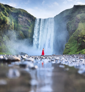 A girl in a red dress on the background of Skogafall waterfall. Journey and adventure in the northern country. Landscape in Iceland