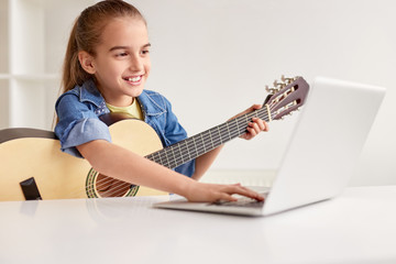 Cheerful girl with guitar using laptop