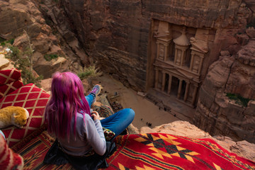 world heritage travel destination photography Middle East Jordan Petra ancient architecture top view girl sitting back to camera on edge of cliff